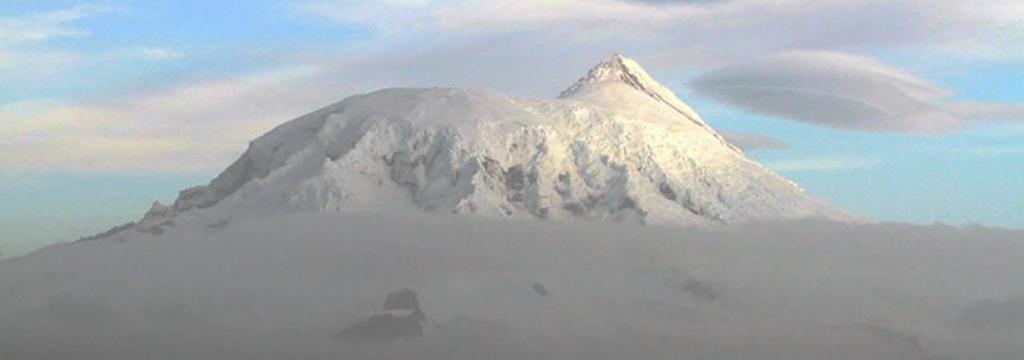 Un volcán erupciona sobre un glaciar